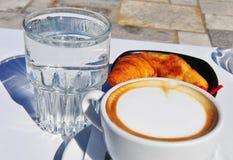 Twee koppen van koffie met croissants en water Stock Foto's