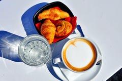 Twee koppen van koffie met croissants en water Royalty-vrije Stock Foto