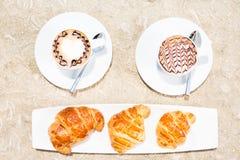 Twee koppen van koffie met lattekunst en croissants Stock Afbeelding