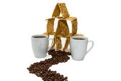 Twee koppen van koffie naast het koekjeshuis, de weg van de ruwe korrels royalty-vrije stock afbeeldingen