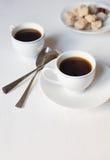 Twee koppen van koffie op de witte lijst en met twee lepels en zo Stock Afbeelding
