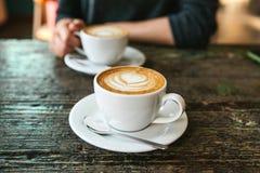 Twee koppen van koffie op een houten lijst, het meisje houdt in haar hand één kop van koffie op de achtergrond Een foto wijst op Royalty-vrije Stock Fotografie