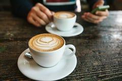 Twee koppen van koffie op een houten lijst, een mens die een telefoon in zijn hand houden en gaan roepen Het wachten op een verga Stock Fotografie