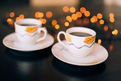 Twee koppen van koffie op lijst aangaande achtergrond bokeh Stock Foto's