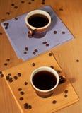 Twee koppen van koffie op servetten met koffiebonen Stock Afbeeldingen