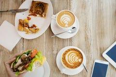 Twee koppen van koffie, vriendschappelijke atmosfeer Kippensandwich, Kop van koffie en smartphone op de lijst Royalty-vrije Stock Afbeelding