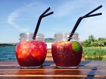 Twee kruiken limonade op houten lijst met meer op de achtergrond stock afbeelding