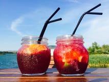 Twee kruiken met limonade op houten lijst met water op de achtergrond royalty-vrije stock foto's