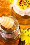 Twee kruiken van honing en gele bloemen Royalty-vrije Stock Foto