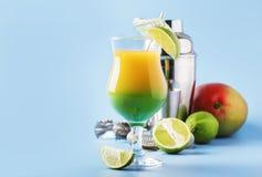Twee-laag alcoholische cocktail met mangosap, rum, likeur, kalk en ijs, de zomer blauwe achtergrond, plaats voor tekst stock fotografie