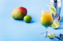 Twee-laag alcoholische cocktail met mangosap, rum, likeur, kalk en ijs, de zomer blauwe achtergrond, plaats voor tekst stock foto's