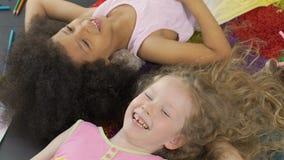 Twee lachende kinderen die op vloer liggen en pret, prachtige tijd hebben die jong zijn stock footage