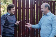 Twee landbouwers die aan elkaar op zonnige dag takling Zij bespreken belangrijk nieuws royalty-vrije stock foto