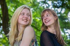 Twee langharige meisjes die aan elkaar lachen royalty-vrije stock foto