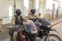Twee leden van de speciale Deltapolitiemachtzitting op hun hoog aangedreven motoren in een zijstraat in Sucre Bolivi? stock foto