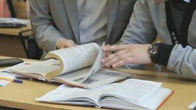 Twee leerlingen knippen pagina's van handboek bij les weg stock videobeelden