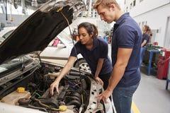 Twee leerlingswerktuigkundigen die de motor in een auto bekijken royalty-vrije stock foto