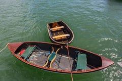 Twee lege die boten voor het opnieuw smelten, op de jachthaven worden vastgelegd stock foto