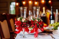 Twee lege die huwelijksglazen, met groen worden verfraaid, rood rozen en lint, die zich op de banketlijst bevinden Stock Fotografie