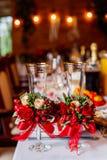 Twee lege die huwelijksglazen, met groen worden verfraaid, rood rozen en lint, die zich op de banketlijst bevinden Royalty-vrije Stock Foto