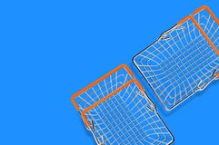 Twee lege die marktmanden van de draad van het chroommetaal en oranje rubber worden gemaakt behandelt het liggen op blauwe lijst  stock fotografie