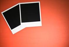 Twee lege onmiddellijke fotokaders op rode achtergrond met exemplaar ruimte hoogste mening Royalty-vrije Stock Foto's