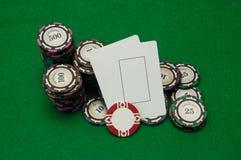 Twee lege spelkaarten met stapels casinospaanders op groen Stock Foto