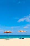 Twee lege sunbeds en strandparasol sunshades op zandstrand Royalty-vrije Stock Afbeelding