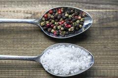 Twee lepels met zoute kristallen en kleurenpeperbollen Royalty-vrije Stock Afbeeldingen