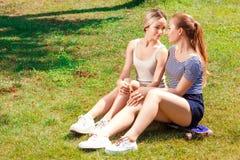 Twee lesbiennes die op gras in park zitten Stock Foto's