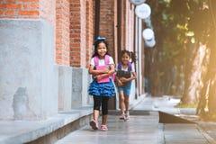 Twee leuke Aziatische kindmeisjes met schooltasholding boeken en lopen samen in de school royalty-vrije stock foto's