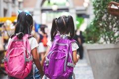 Twee leuke Aziatische kindmeisjes met schooltasholding overhandigen en lopen samen in de school royalty-vrije stock foto's