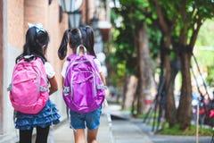 Twee leuke Aziatische kindmeisjes met schooltasholding overhandigen en lopen samen in de school royalty-vrije stock afbeeldingen