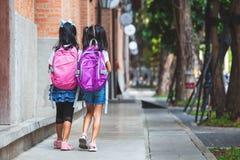 Twee leuke Aziatische kindmeisjes met schooltasholding overhandigen en lopen samen in de school stock afbeeldingen