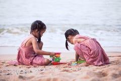 Twee leuke Aziatische kleine kindmeisjes die pret met zand hebben te spelen stock afbeeldingen