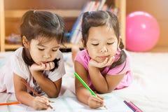 Twee leuke Aziatische meisjes rusten hun kin op hun handen Stock Foto