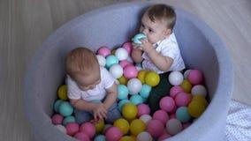 Twee leuke jonge geitjes die in een pool van kleurrijke plastic ballen spelen stock footage
