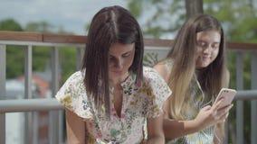 Twee leuke jonge studentes die in openlucht samen zitten Één meisje die aan muziek met haar hoofdtelefoons luisteren, tweede  stock video