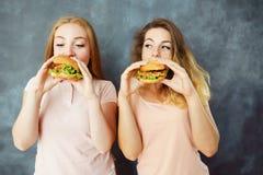 Twee leuke jonge vrouwen die heerlijke burgers eten royalty-vrije stock foto's