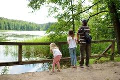 Twee leuke jonge zusters die door een meer in een bos met hun vader op mooie de zomerdag wandelen stock foto's