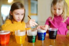 Twee leuke jonge zusters die paaseieren thuis verven Kinderen die kleurrijke eieren voor Pasen-jacht schilderen Jonge geitjes die royalty-vrije stock afbeeldingen