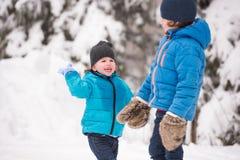 Twee leuke jongens die buiten in de winteraard spelen stock afbeeldingen