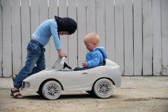 Twee Leuke jongensspelen met een stuk speelgoed auto Royalty-vrije Stock Foto's