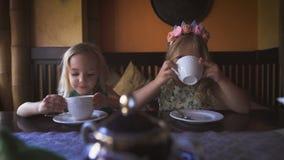 Twee leuke kleine blondemeisjes hebben thee in een comfortabele koffie stock footage