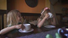 Twee leuke kleine blondemeisjes hebben thee in een comfortabele moderne koffie stock footage