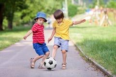 Twee leuke kleine jonge geitjes, speelvoetbal samen, zomer stock foto