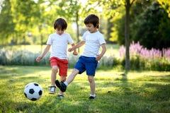 Twee leuke kleine jonge geitjes, speelvoetbal samen, zomer chi Stock Afbeelding