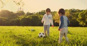 Twee leuke kleine jonge geitjes, speelvoetbal samen, zomer Kinderen die voetbal spelen openlucht stock videobeelden