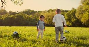 Twee leuke kleine jonge geitjes, speelvoetbal samen, zomer Kinderen die voetbal spelen openlucht stock video