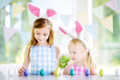 Twee leuke kleine zusters die konijntjesoren dragen die eijacht op Pasen spelen Stock Afbeelding